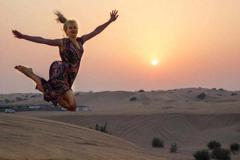 a_blonde_girl_jumping_in_sunset_light