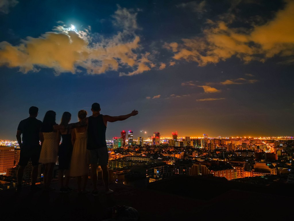 a_group_of_friends_standing_at_The_top_of_a_high_building_with_a_view_to_a_night_barcelona