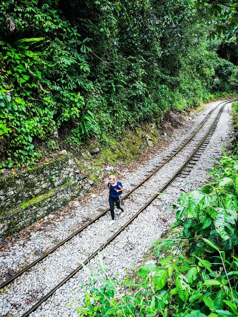 a_blonde_traveler_walking_on_a_railway