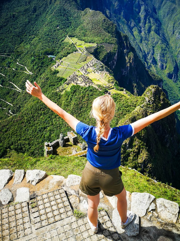 s_blonde_girl_standing_at_the_top_of_huayna_picchu_with_a_view_to_machu_picchu