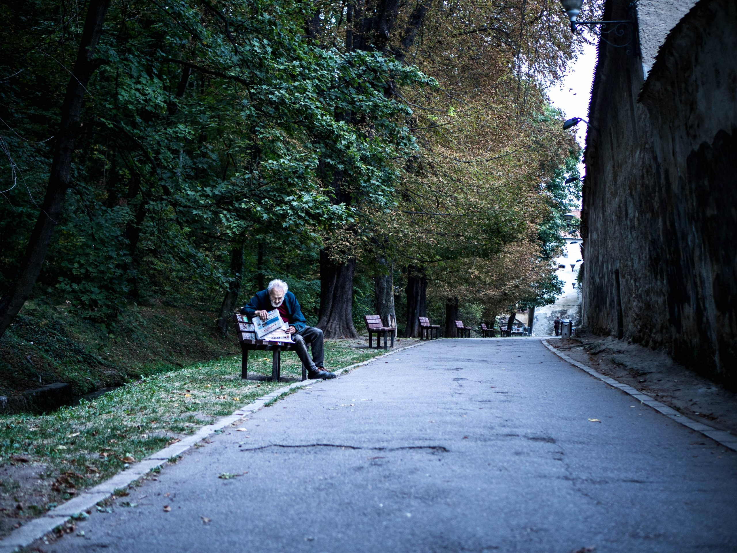 old-man-sitting-in-wodden-bench-reading-a-magazine