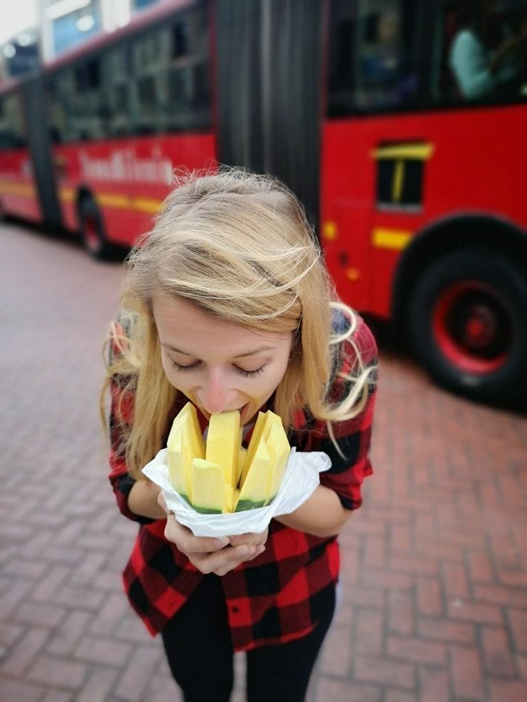 blonde-girl-eating-mango-on-bus-station