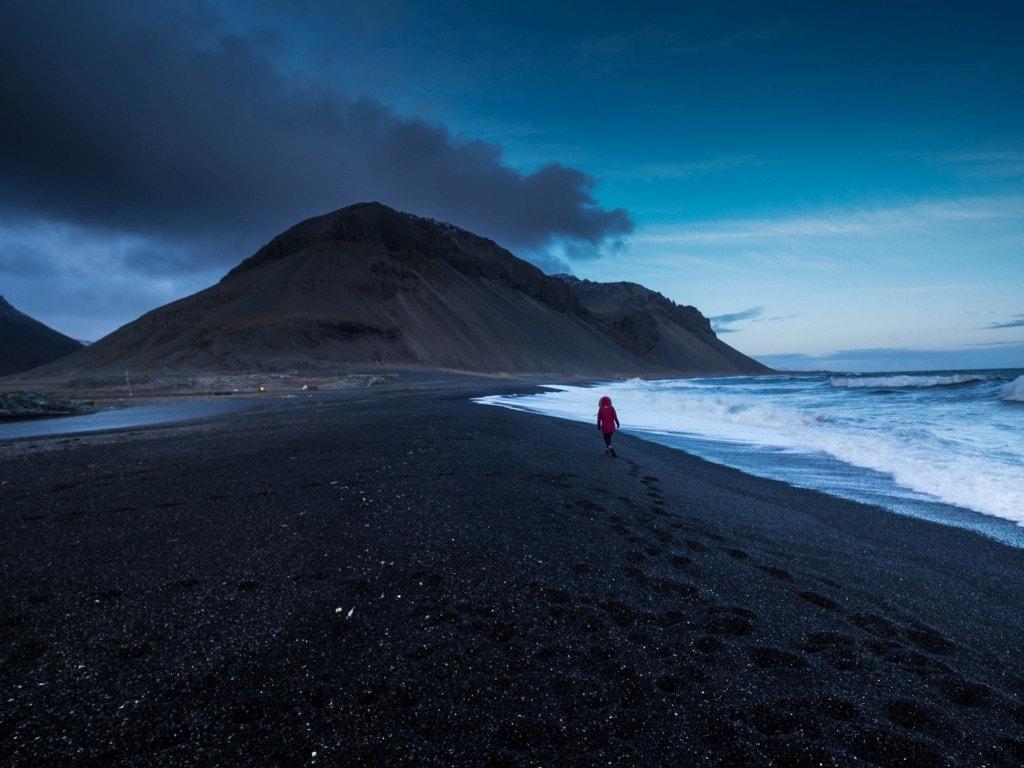 girl walking on a volcanic blacj beach