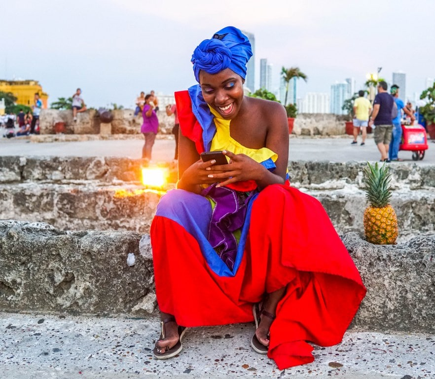 colombian woman in a colourful traditional dress sitting on a ground with a phone in her hands