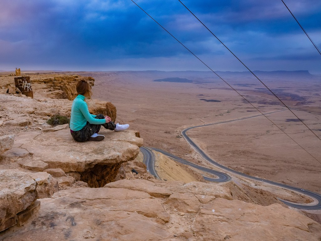 a_blonde_girl_sitting_on_the_edge_of_a_dry_cliff