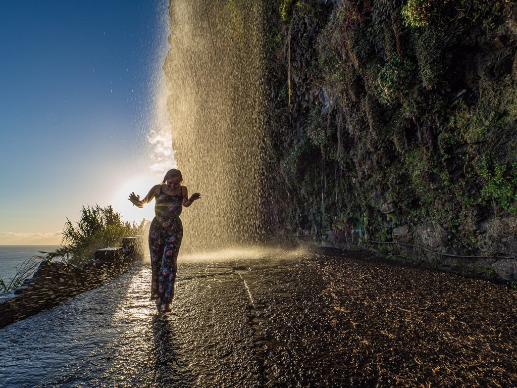 a_girl_standing_and_smilling_in_the_middle_of_a_waterfall