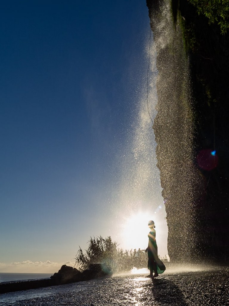 a_gril_standing_in_the_middle_of_a_waterfall