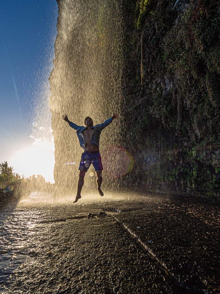 a_men_happilly_jumping_in_the_middle_of_a_waterfall