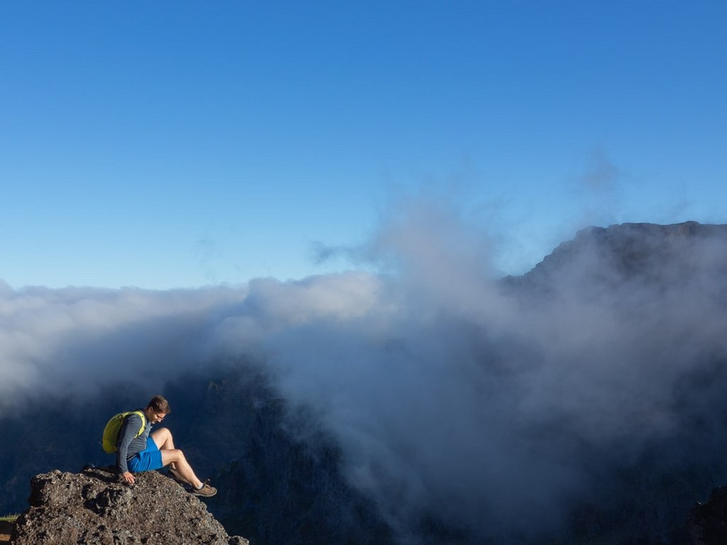 a_men_sitting_on_a_top_of_a_rock_in_madeiras_moutains_surrounded_with_clouds
