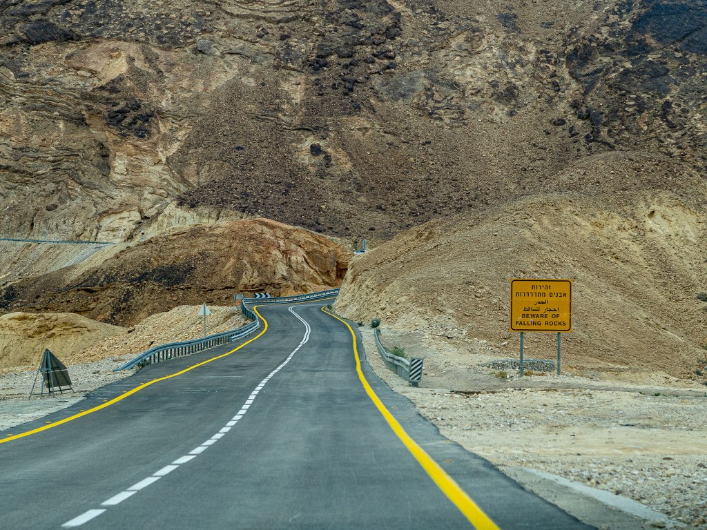 a_wide_road_with_yellow_marks_leading_to_a_deserted_area_in_israel