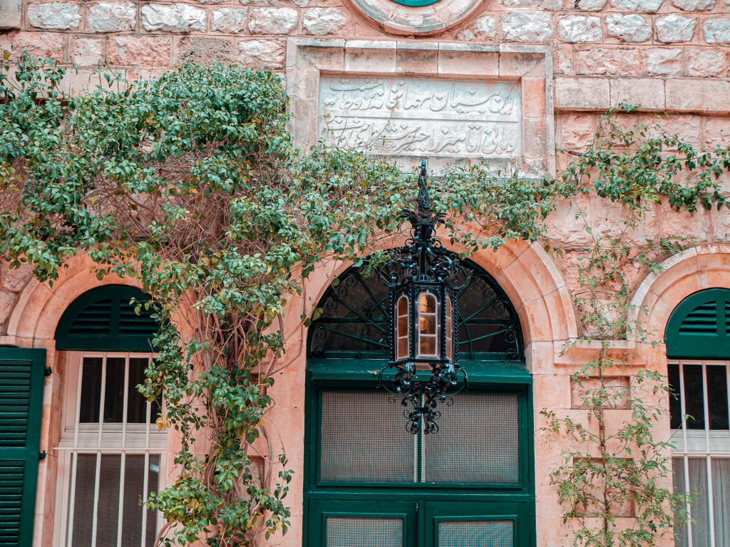 orange_bricked_bulding_covered_with_green_plants