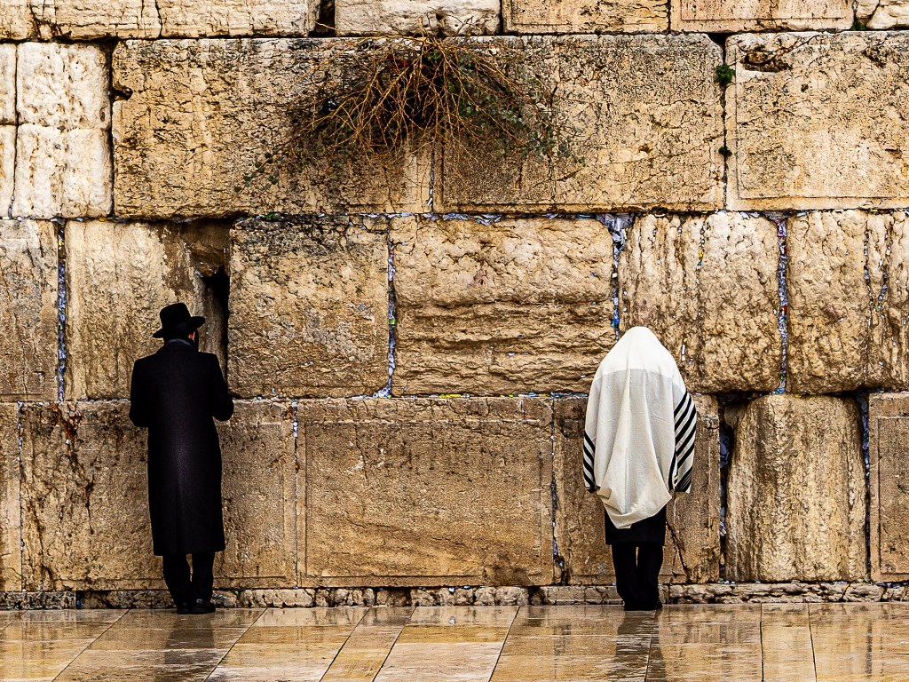 two_orthodox_jews_praying_in_front_of_the_western_wall_in_jerusalem
