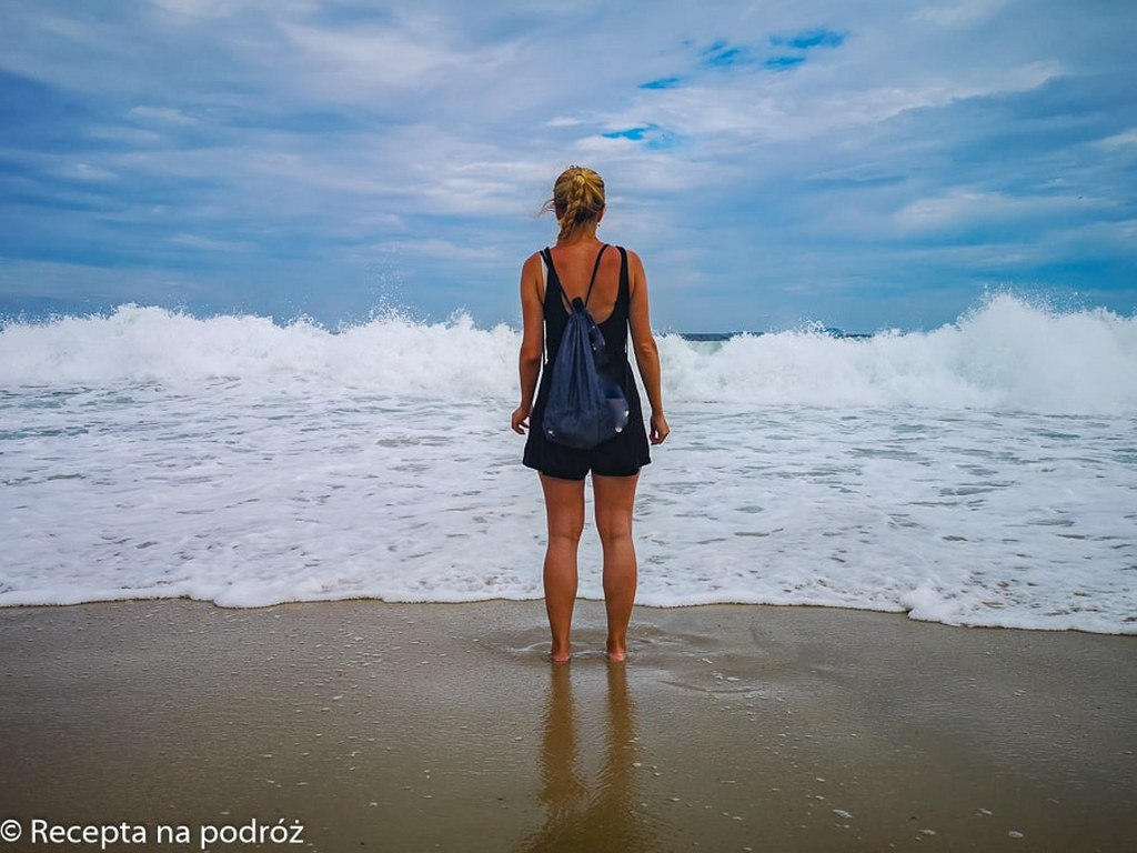 a_blonde_girl_standing_in_front_of_the_atlantic_ocean_waves