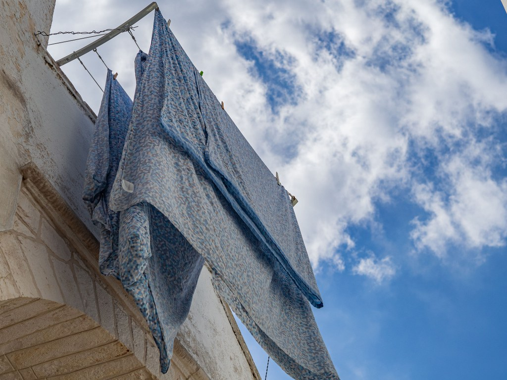 blue_bed_sheets_waving_on_the_wind_from_a_balcony